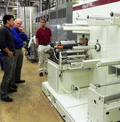 Roland Gong, Assistant Professor for Paper Science & Engineering; Rick Ruenzel, Sales Engineer for Faustel; and Paul Fowler, Executive Director of the Wisconsin Institute for Sustainable Technology inspect the newly installed LabMaster Pilot Coater.